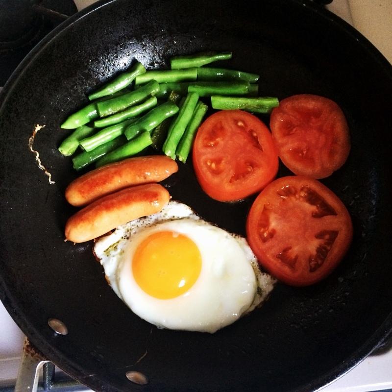 野菜とソーセージと目玉焼きを時間差で焼いていきます。