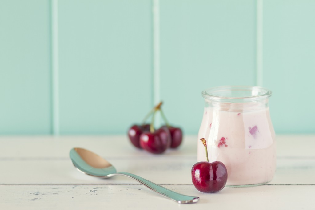 A jar with cherry yogurt and some cherries in a white wooden table with a robin egg blue background. Vintage style.