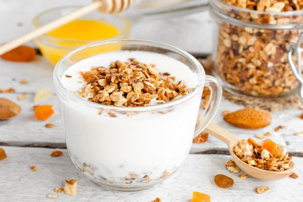 yogurt with homemade granola, nuts and dried fruits in a glass cup