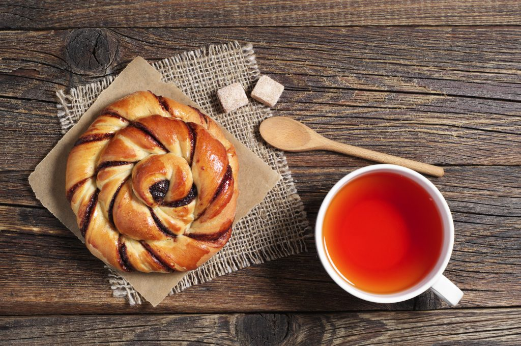 Cup of hot tea and sweet bun with jam on old wooden table, top view