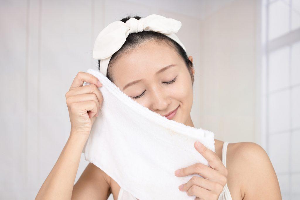 蒸しタオルでスキンケアする女性の画像
