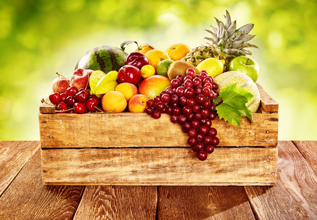 Wooden crate filled with a wide assortment of fresh healthy tropical fruit on a rustic wood table outdoors with sunlit blurred green background
