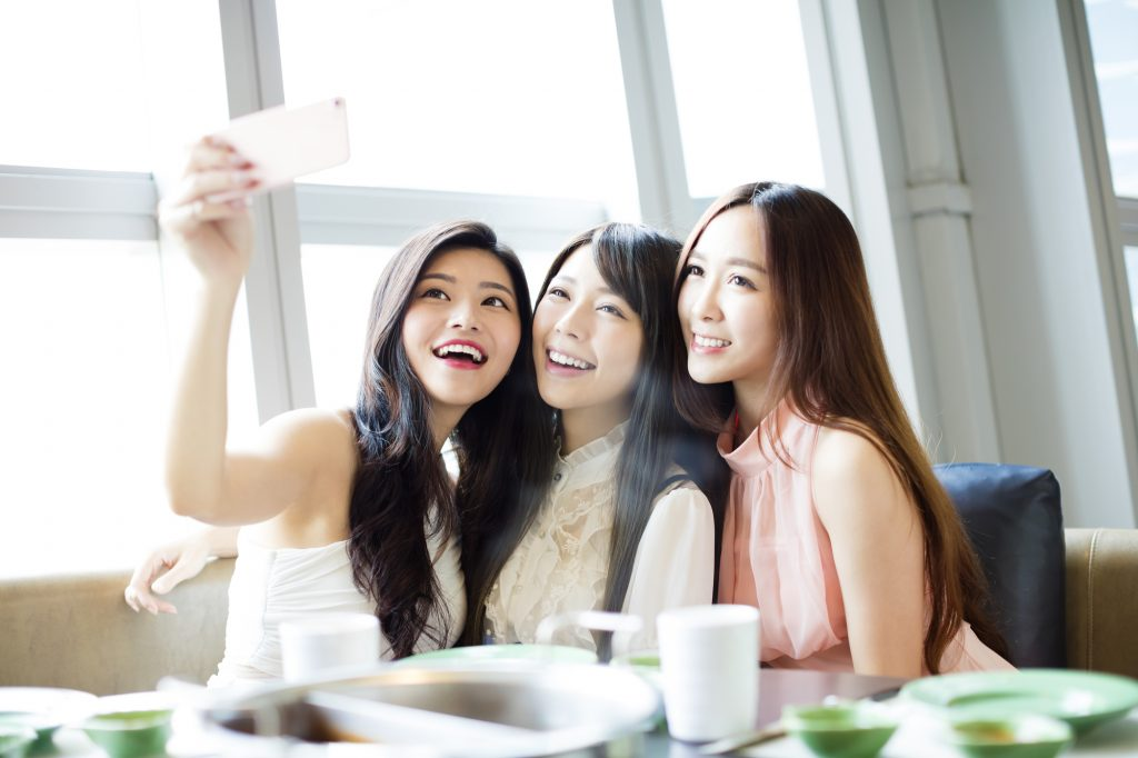 happy young girl friend taking selfie together in restaurant