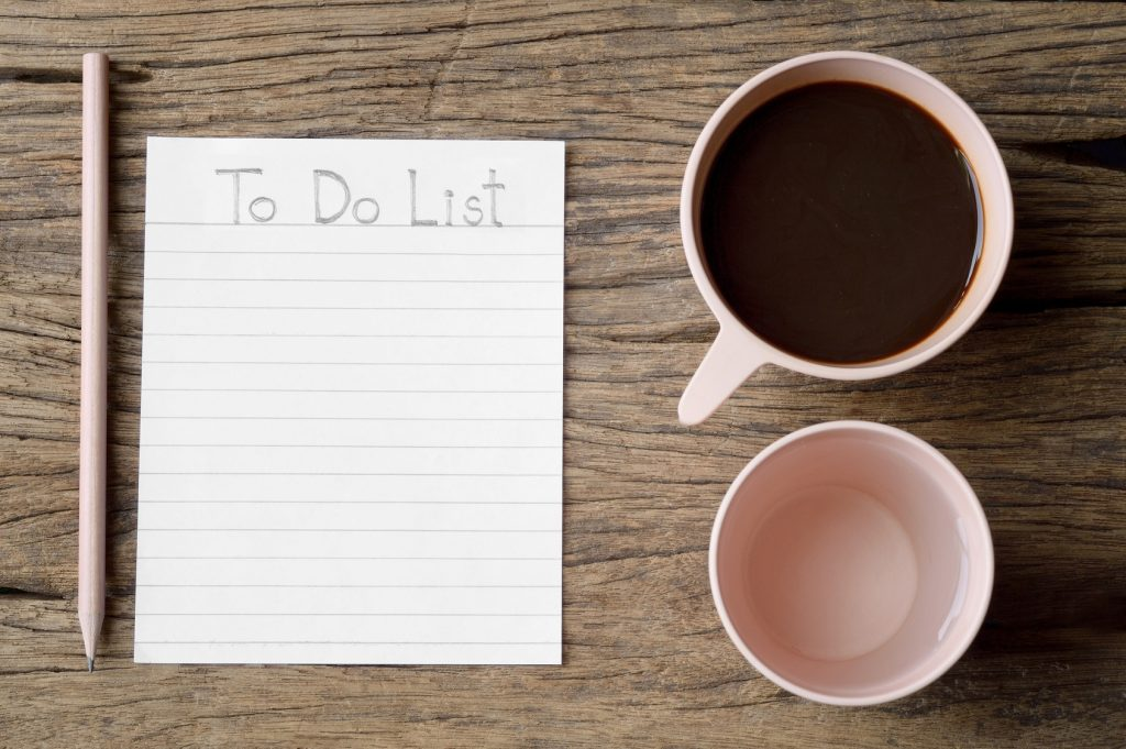 to do list word on wooden table with coffee cup, drinking water and pencil