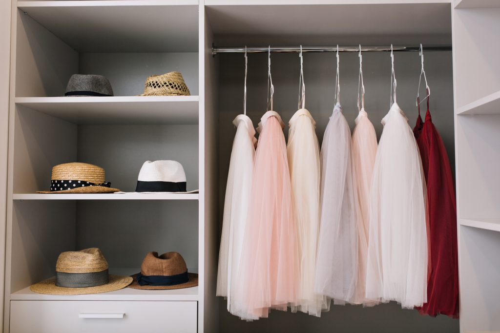 Modern bright dressing room with shelves. Fashionable hats, beautiful pink and red dresses hanging in wardrobe