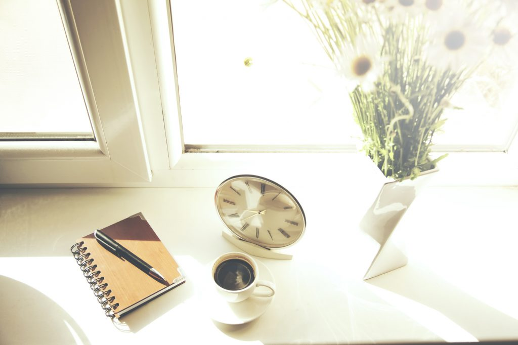 clock, notebook,coffee and flower on window