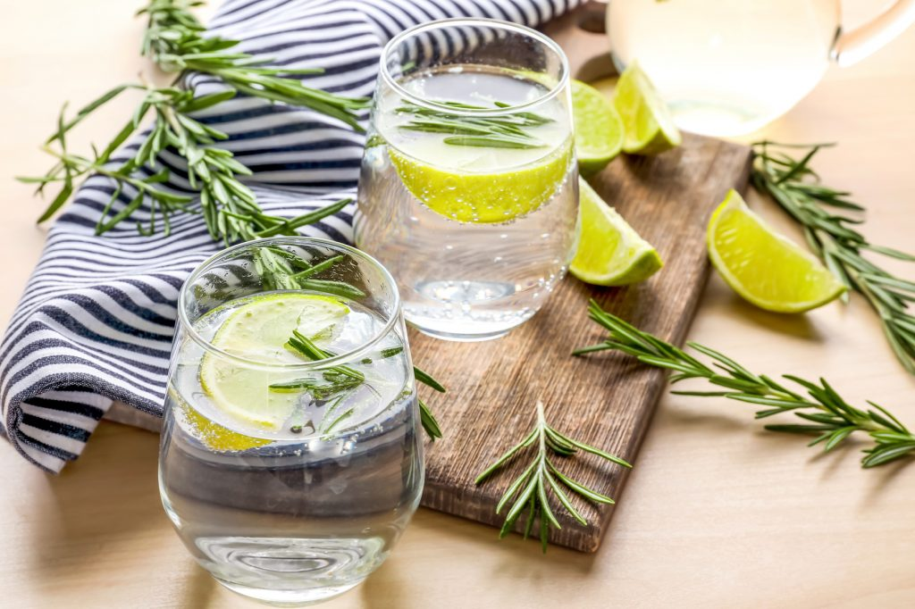 Glasses of fresh lime lemonade with rosemary on table