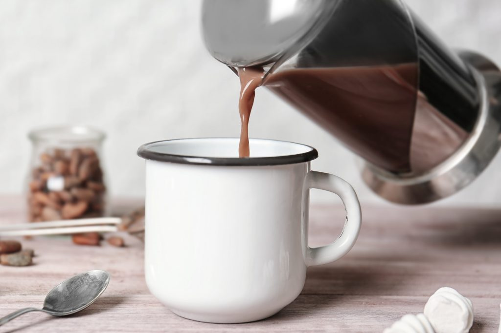 Pouring hot cocoa drink into metal mug on kitchen table