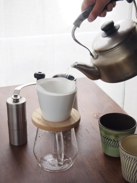 コーヒーを淹れるためにやかんから注ぐお湯