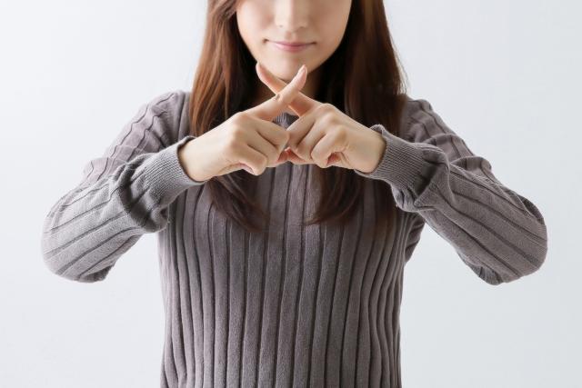 「Stop!」のジェスチャーをする女性