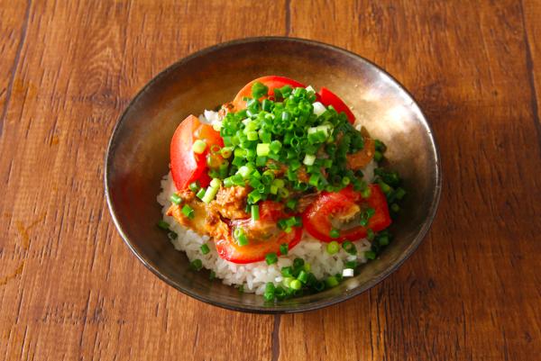 サバ缶を缶詰の中でスプーンで大きめにほぐしてご飯にのせ、トマトをのせて青ネギを散らす。