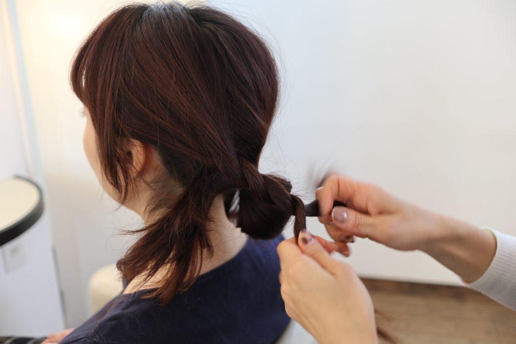 サイドの残った髪を片方ずつロープ編みにしながら、(3)で結んだゴムに挟み込んで留めます。
