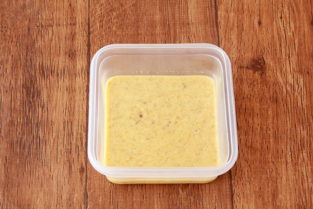 保存容器にバナナを入れてフォークでつぶし、卵、プレーンヨーグルト、オリーブオイルを加えて混ぜる。
