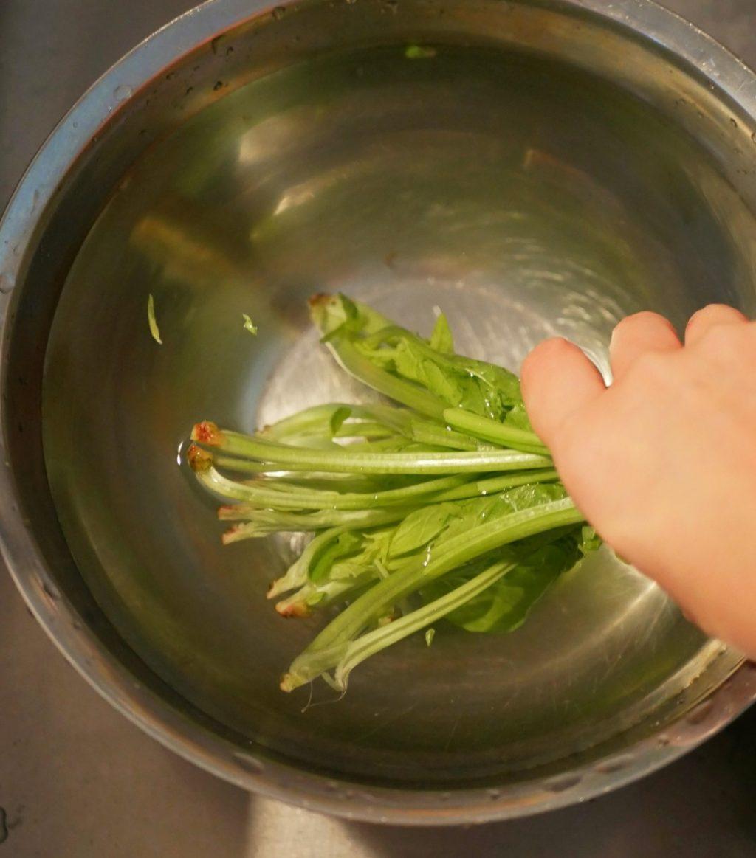ほうれん草は茎に十字に切り込みを入れて、水を張ったボウルに入れて、しっかりと洗う