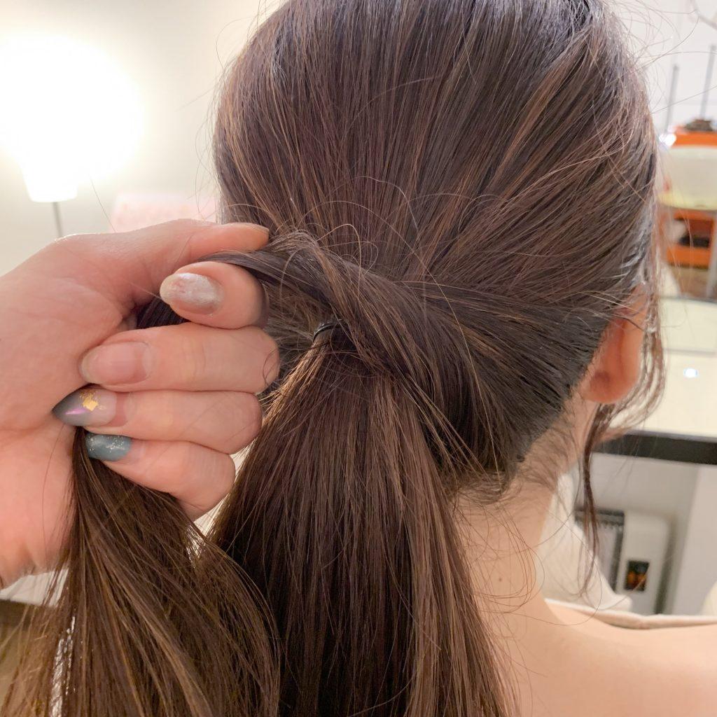 下の残った髪をねじりながら、上の結び目を隠すように巻き付けます。