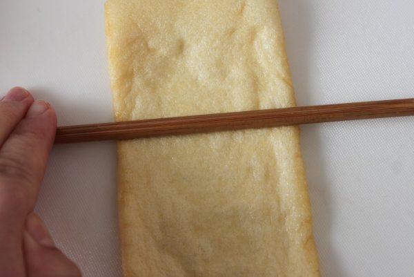 薄揚げをまな板に置き、さいばし等で上からコロコロと少し力を入れて転がす(こうすると、中がはがれやすくなります)。