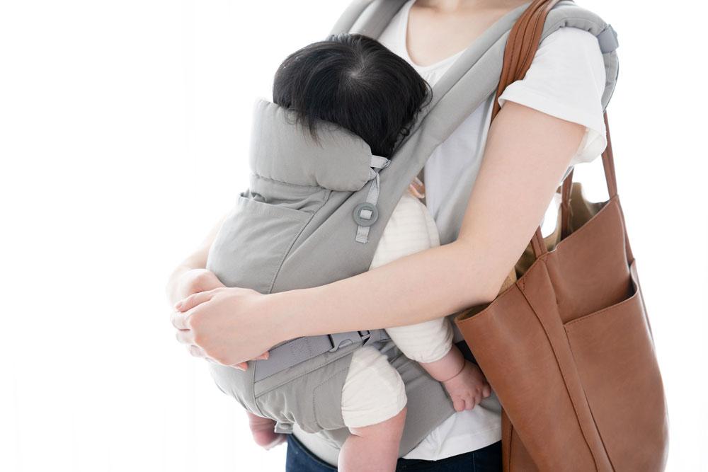 抱っこ紐で赤ちゃんを抱っこする女性