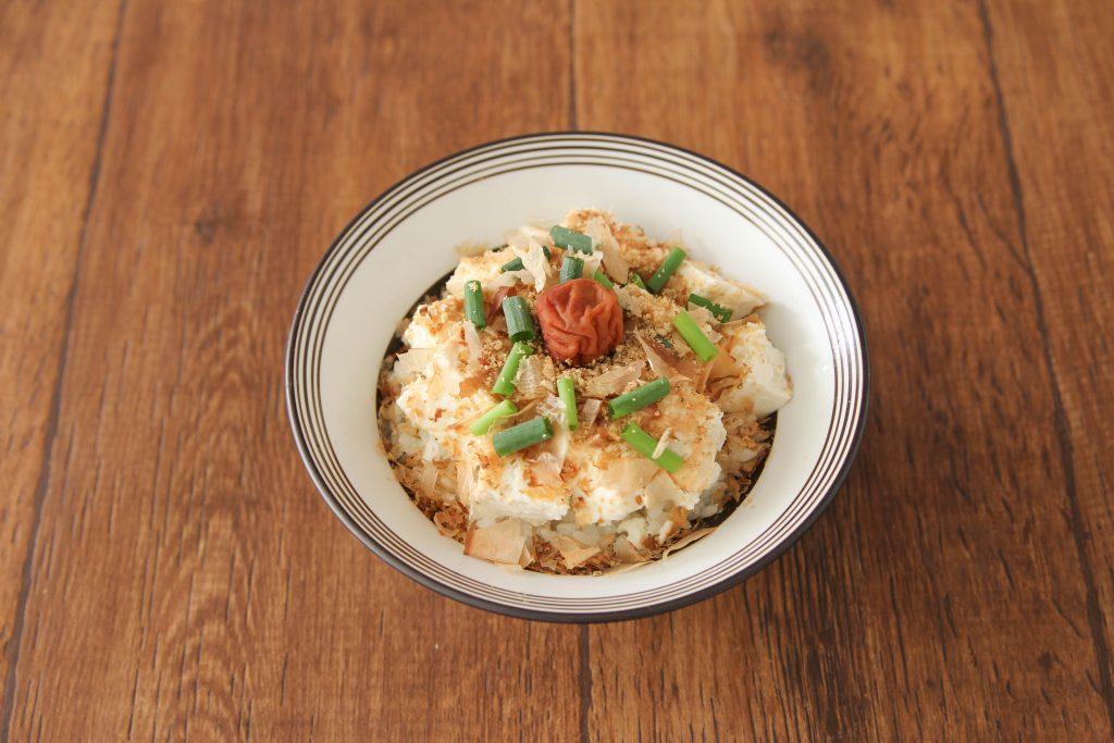 豆腐を手で軽く握って水気を切り、一口サイズにちぎってご飯にのせる。かつお節をのせて青ネギをキッチンバサミで切って散らし、白すりごまをかけて梅干しを中央にのせ、めんつゆをかける