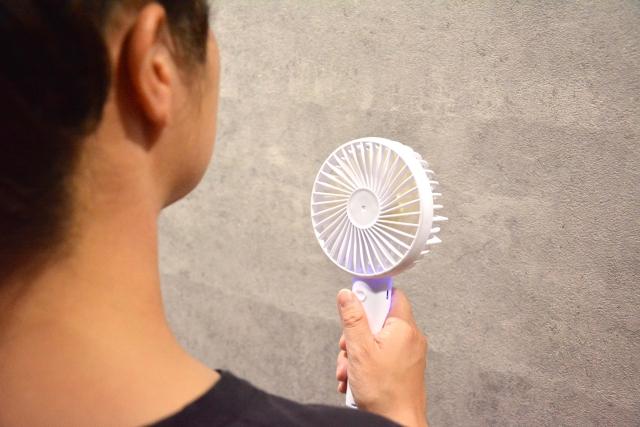 小型扇風機を使う女性