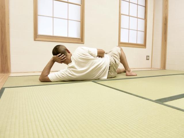 畳で横になる男性