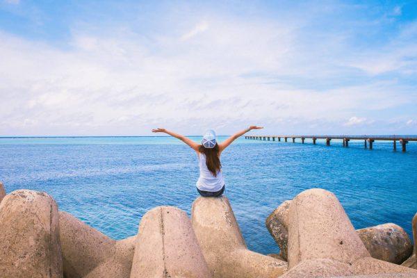 海辺で背伸びする女性