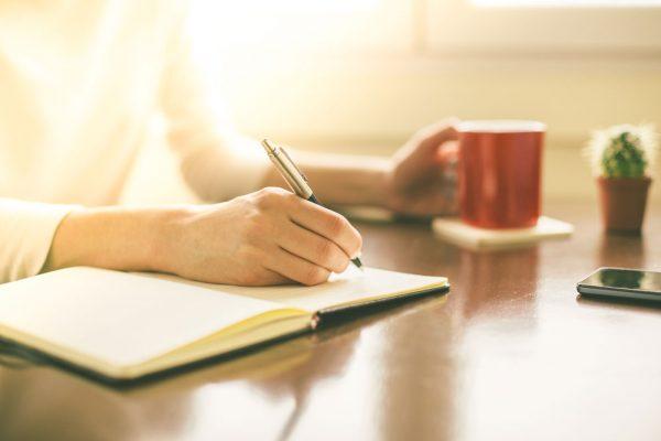 ノートを書く女性の手