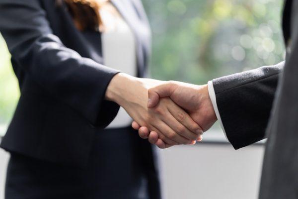取引先と握手する女性