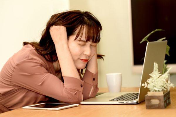 仕事中に頭を抱える女性