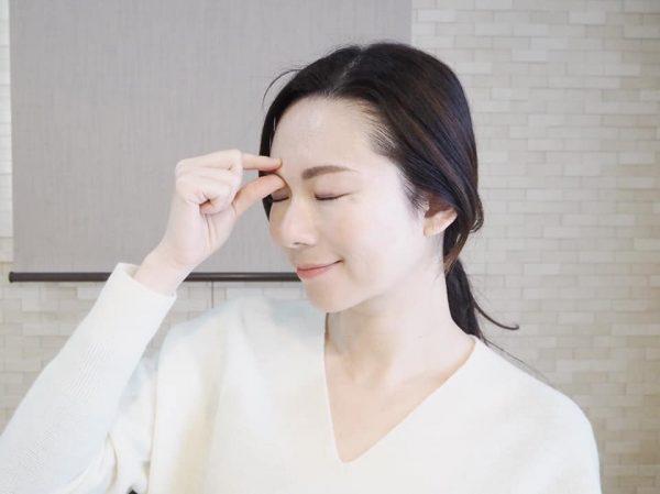 目のマッサージをする女性