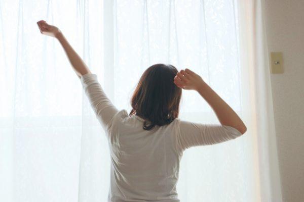 朝起きて伸びをする女性