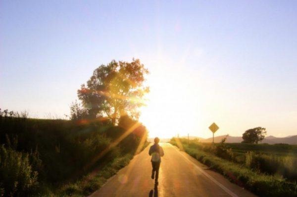 朝日の中を走る女性