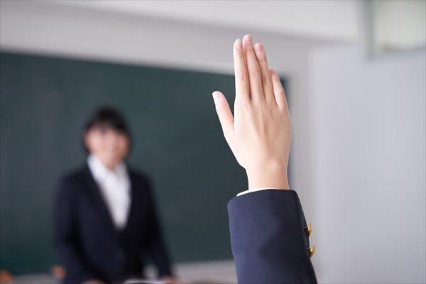 教室で手を挙げる生徒