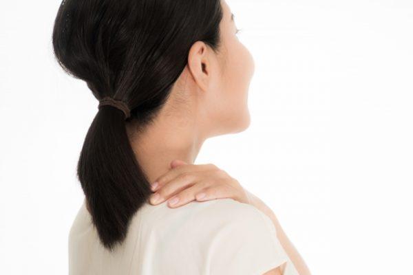 肩をおさえる女性