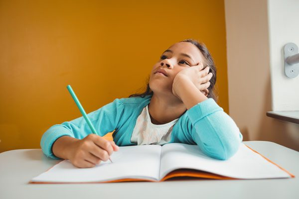 ノートに書くことを考えている女の子