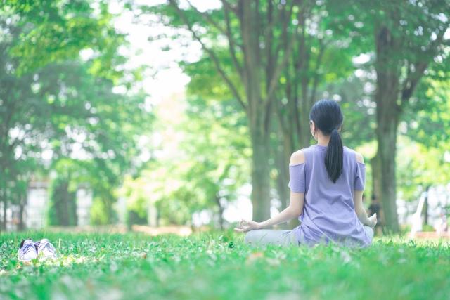 朝に公園で瞑想する女性