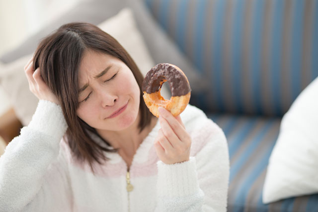 ドーナツを持って悩む女性